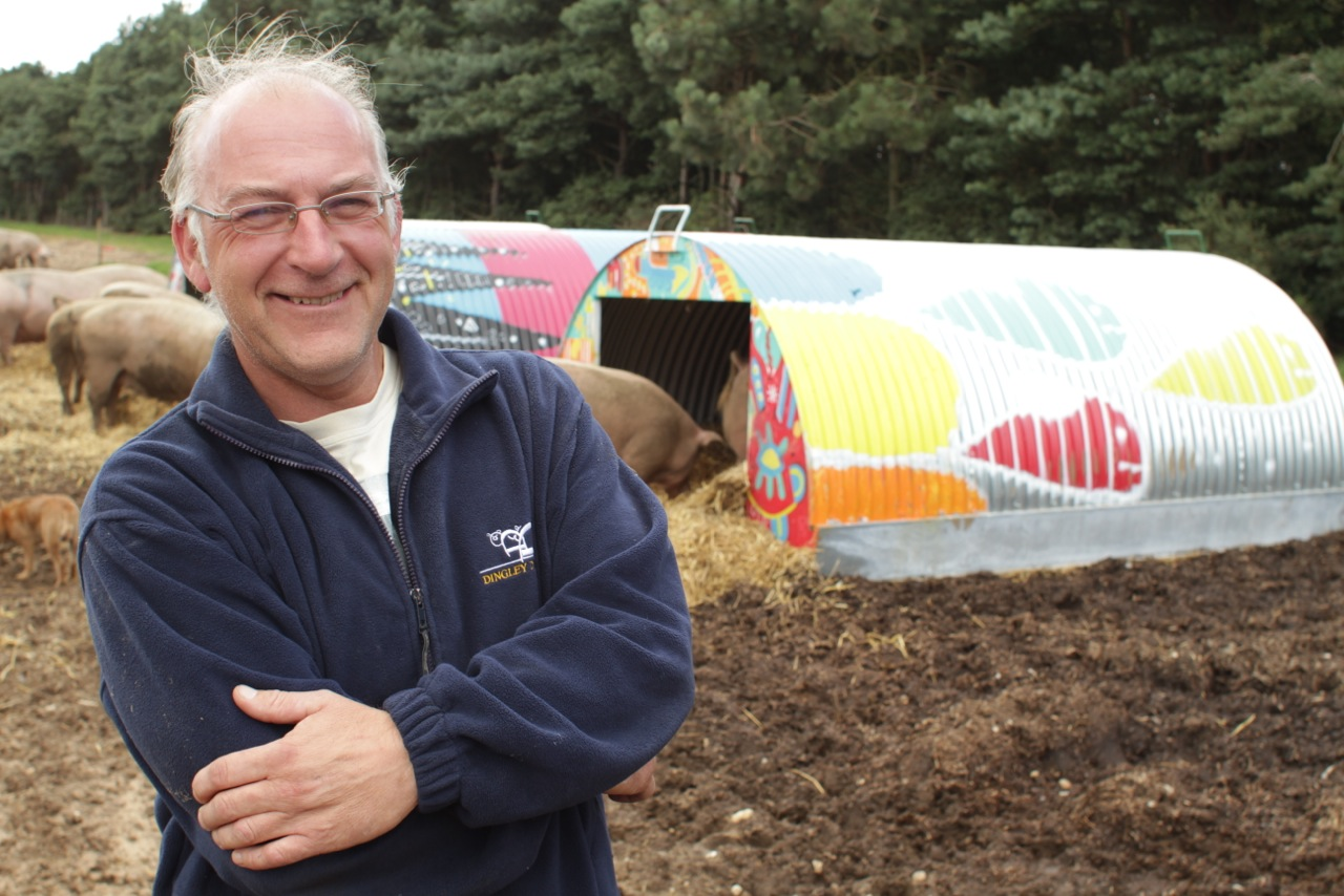 Mark Hayward, partner at Dingley Dell Pork, stands outside one of his brightly coloured pig huts